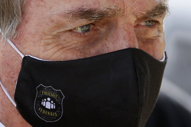 Brazil's President Jair Bolsonaro, wearing a face mask with a logo reading in Portuguese