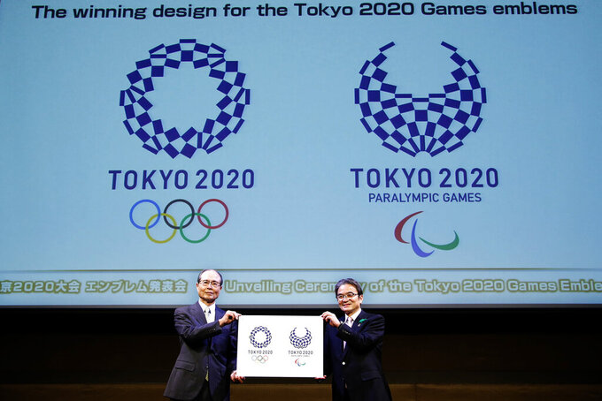 FILE - In this April 25, 2016, file photo, Tokyo 2020 Emblems Selection Committee Chairperson Ryohei Miyata, right, and its member and Japanese baseball great Sadaharu Oh hold new official logos of the 2020 Tokyo Olympics, left, and the 2020 Tokyo Paralympic Games during the unveiling ceremony in Tokyo. (AP Photo/Shizuo Kambayashi, File)