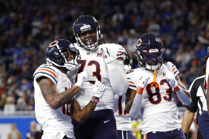 Chicago Bears wide receiver Allen Robinson, left, and teammates offensive tackle Cornelius Lucas (73) and wide receiver Javon Wims (83) celebrate Robinson's 10-yard reception for a touchdown during the first half of an NFL football game, Thursday, Nov. 28, 2019, in Detroit. (AP Photo/Rick Osentoski)