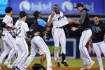 Miami Marlins' Bryan De La Cruz, center, is mobbed by teammates after he hit a single scoring Jazz Chisholm Jr. to beat the New York Mets 2-1 in 10 innings of a baseball game, Wednesday, Sept. 8, 2021, in Miami. (AP Photo/Wilfredo Lee)