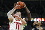 Michigan State forward Gabe Brown, center, grabs a rebound next to Wisconsin forward Micah Potter (11) during the first half of an NCAA college basketball game, Friday, Jan. 17, 2020, in East Lansing, Mich. (AP Photo/Carlos Osorio)