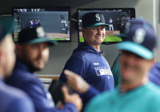 FILE - In this April 12, 2019 file photo, Seattle Mariners manager Scott Servais, center, smiles in the dugout before a baseball game against the Houston Astros in Seattle. Spring training for the Mariners ahead of the 2020 season will feature young players and prospects that could be at the heart of whether the Mariners' rebuild plans ultimately work. (AP Photo/Ted S. Warren, File)