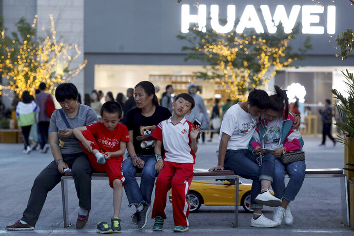 In this photo taken Monday, May 20, 2019, residents enjoy a cool evening near a Huawei store in Beijing. The Trump administration's sanctions against Huawei have begun to bite even though their dimensions remain unclear. U.S. companies that supply the Chinese tech powerhouse with computer chips saw their stock prices slump Monday, and Huawei faces decimated smartphone sales with the anticipated loss of Google's popular software and services. (AP Photo/Ng Han Guan)