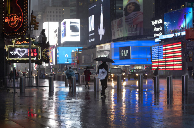 FILE - In this Nov. 30, 2020, file photo, shoppers walk in a rainstorm through New York's Times Square. The job market is slowing down as the fall surge in the virus puts severe strain on the economy and health care system. (AP Photo/Mark Lennihan)