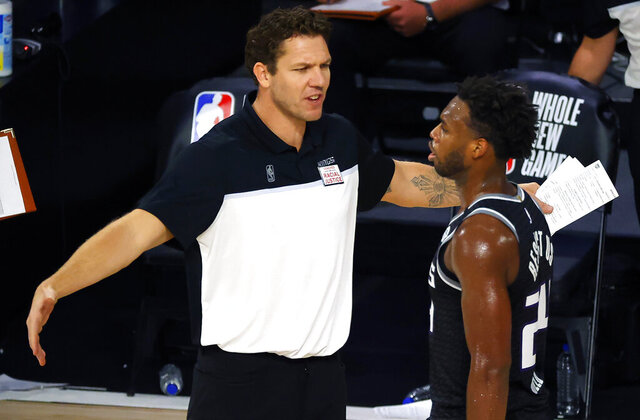 FILE - In this Thursday, Aug. 13, 2020, file photo, Sacramento Kings head coach Luke Walton, left, talks with Buddy Hield during the fourth quarter of an NBA basketball game against the Los Angeles Lakers, in Lake Buena Vista, Fla. The hope for the Sacramento Kings' 2020-21 season is that speeding up their play on the court will help quicken the turnaround for a franchise that hasn't been to the playoffs since 2006. (Kevin C. Cox/Pool Photo via AP, File)