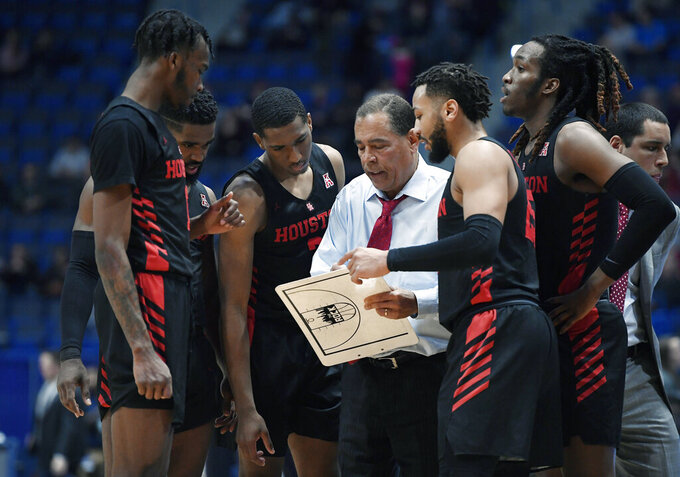 FILE - In this Feb. 14, 2019, file photo, Houston head coach Kelvin Sampson talks to his team during the first half of an NCAA college basketball game against Connecticut, in Hartford, Conn. The entire team piles into Sampson's house before each home game to prepare for the next opponent, eat his wife Karen's delicious homemade chocolate chip cookies and bond like a family. The routine is something Sampson and his players agree has created an environment of closeness and trust that is an integral ingredient in the ninth-ranked Cougars' success this season.(AP Photo/Jessica Hill, File)