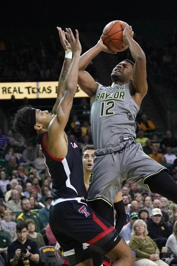 FILE - In this March 2, 2020, file photo, Baylor's Jared Butler (12) shoots against Texas Tech's Terrence Shannon Jr. during the first half of an NCAA college basketball game in Waco, Texas. Baylor All-Big 12 guard Jared Butler plans to enter his name into the NBA draft pool while keeping open his options to return to the Bears for his junior season. Butler announced his intentions in a Twitter post Monday, April 20, 2020. (AP Photo/Chuck Burton, File)