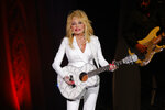 """FILE - Dolly Parton performs in concert on July 31, 2015, in Nashville, Tenn. The Grammy-winning legend's 1980's hit """"9 to 5"""" has been flipped by Squarespace, the company that helps users build and host their own websites, for a Super Bowl commercial debuting Tuesday, Feb. 2, 2021. Oscar winner Damien Chazelle of """"La La Land"""" fame directed the spot. (Photo by Wade Payne/Invision/AP, File)"""