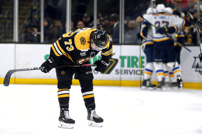 Boston Bruins' Charlie McAvoy reacts as the St. Louis Blues' celebrate Brayden Schenn's goal, right, during the third period in Game 7 of the NHL hockey Stanley Cup Final, Wednesday, June 12, 2019, in Boston. (AP Photo/Michael Dwyer)