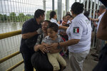 A Honduras migrant mother and her son walk through the bridge after crossing the border between Guatemala and Mexico, in Ciudad Hidalgo, Mexico, Saturday, Oct. 20, 2018. Mexican officials are refusing to yield to demands from the caravan of Central American migrants that they be allowed to enter the country en masse but announced they would hand out numbers to those waiting to cross and allow them to enter in small groups. (AP Photo/Oliver de Ros)