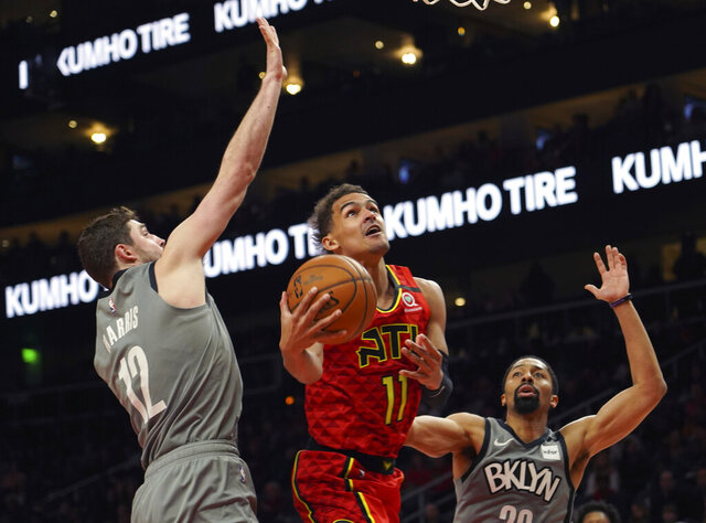 FILE - Atlanta Hawks guard Trae Young (11) drives to the basket between Brooklyn Nets forward Joe Harris (12) and Spencer Dinwiddie in the second half of an NBA basketball game in Atlanta, in this Friday, Feb. 28, 2020, file photo. Hawks All-Star Trae Young and his high-scoring sidekick John Collins are entering a new season with a strong surge of new help as they adjust to the additions of Danilo Gallinari, Bogdan Bogdanovic, Kris Dunn and Rajon Rando. The offseason moves have made Atlanta a playoff contender. (AP Photo/Tami Chappell, File)