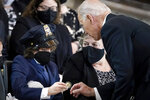 """President Joe Biden gives a coin to Logan Evans, son of late U.S. Capitol Police officer William """"Billy"""" Evans, during a memorial service as Evans lies in honor in the Rotunda at the U.S. Capitol, Tuesday, April 13, 2021 in Washington. (Drew Angerer/Pool via AP)"""