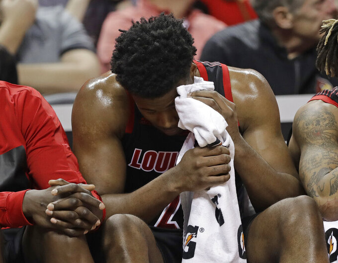 Louisville's Steven Enoch holds a towel to his eye after being injured during the second half of an NCAA college basketball game against North Carolina in the Atlantic Coast Conference tournament in Charlotte, N.C., Thursday, March 14, 2019. (AP Photo/Chuck Burton)