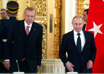 Turkish President Recep Tayyip Erdogan, left, and Russian President Vladimir Putin arrive for a meeting with businessmen in the Kremlin in Moscow, Russia, Monday, April 8, 2019. Russian President Vladimir Putin on Monday hosted Turkish counterpart Recep Tayyip Erdogan for talks focusing on the situation in Syria, the sale of advanced Russian missiles to Turkey and other economic deals. (Maxim Shipenkov/Pool Photo via AP)