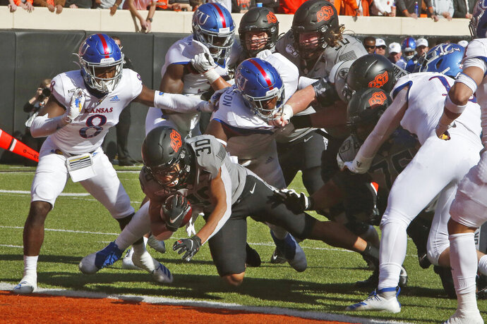 Oklahoma State running back Chuba Hubbard (30) dives into the end zone for a touchdown in front of half of Kansas cornerback Kyle Mayberry (8) and defensive tackle Caleb Sampson, center, in the first half an NCAA college football game in Stillwater, Okla., Saturday, Nov. 16, 2019. (AP Photo/Sue Ogrocki)