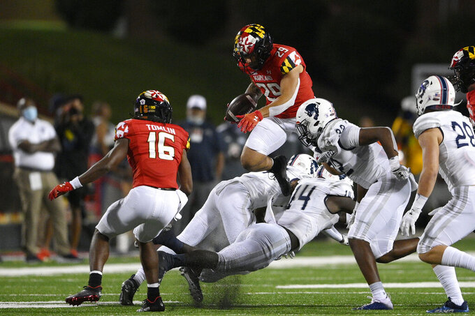 Maryland running back Challen Faamatau (29) leaps with the ball against Howard defensive back Kenny Gallop (14) during the second half of an NCAA college football game, Saturday, Sept. 11, 2021, in College Park, Md. Maryland wide receiver Dino Tomlin (16) looks on. (AP Photo/Nick Wass)