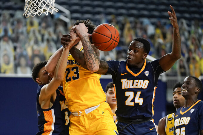 Michigan forward Brandon Johns Jr. (23) battles with Toledo guard Ryan Rollins (5) and Keshaun Saunders (24) for a rebound in the second half of an NCAA college basketball game in Ann Arbor, Mich., Wednesday, Dec. 9, 2020. Michigan won 91-71. (AP Photo/Paul Sancya)