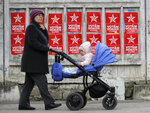 A woman pushes a baby stroller by electoral posters advertising the candidates of the Socialists' Party, in Chisinau, Moldova, Thursday, Feb. 21, 2019, ahead of parliamentary elections taking place on Feb. 24. Moldova's president says the former Soviet republic needs good relations with Russia, amid uncertainty about the future of the European Union. (AP Photo/Vadim Ghirda)