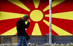 A man walks past the national flag set in a street in Skopje, North Macedonia, Friday, April 19, 2019. North Macedonia holds the first round of presidential elections on Sunday, a vote seen as key test for the center-left government's survival in a society deeply divided after the country changed its name to end a decades-old dispute with neighboring Greece over use of the term