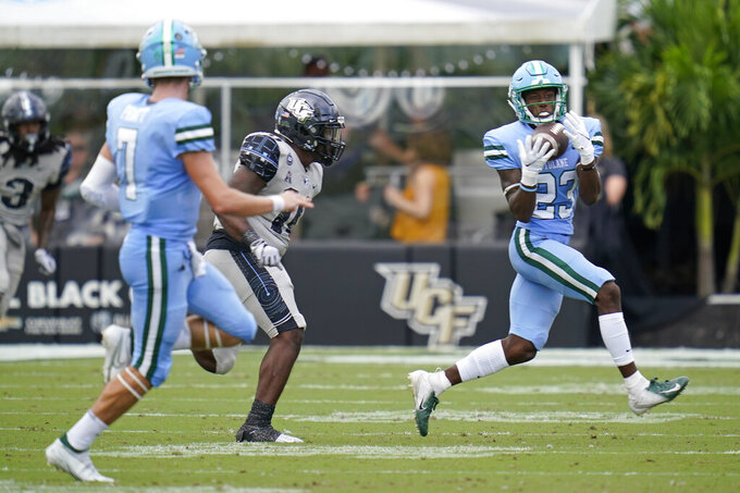 Tulane wide receiver Jaetavian Toles (23) makes a reception off a pass from quarterback Michael Pratt (7) as Central Florida linebacker Eriq Gilyard, center, tries to defend during the first half of an NCAA college football game, Saturday, Oct. 24, 2020, in Orlando, Fla. (AP Photo/John Raoux)