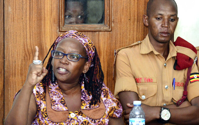 In this photo taken on Monday April 10, 2017, Makerere University researcher Dr Stella Nyanzi, left, gestures in the dock at Buganda Road Court in the capital Kampala, Uganda.  The Ugandan academic Nyanzi, who was imprisoned after insulting the president was freed Thursday Feb. 20, 2020, by a judge who said she had been wrongfully convicted. Frank Baine, a spokesman for the prisons service, said Stella Nyanzi was driven back to the maximum-security prison to collect her belongings after the high court ordered her release. (AP Photo)