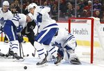 Toronto Maple Leafs defenseman Cody Ceci, right, goes after the puck as Maple Leafs defenseman Morgan Rielly (44) and Arizona Coyotes center Barrett Hayton (29) battle during the first period of an NHL hockey game Thursday, Nov. 21, 2019, in Glendale, Ariz. (AP Photo/Ross D. Franklin)