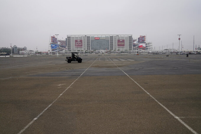 A cart drives through an empty area of the Levi's Stadium parking lot before an NFL football game between the San Francisco 49ers and the Arizona Cardinals in Santa Clara, Calif., Sunday, Sept. 13, 2020. (AP Photo/Tony Avelar)