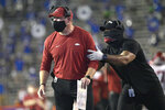 Acting Arkansas coach Barry Odom, left, is pulled back to the sideline by an assistant during the second half of the team's NCAA college football game against Florida, Saturday, Nov. 14, 2020, in Gainesville, Fla. (AP Photo/Phelan M. Ebenhack)