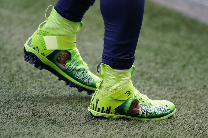 Seattle Seahawks quarterback Russell Wilson wears custom cleats with the name of Breonna Taylor and others  in support of Black Lives Matter as he warms up for an NFL football game against the New York Giants, Sunday, Dec. 6, 2020, in Seattle. Five years ago, about 500 players participated in the inaugural campaign, marking the first time players could wear custom cleats during games without facing fines. This year, more than 1,000 players took part, wearing their cleats during Week 13 games to raise awareness and funds for various causes. (AP Photo/Elaine Thompson)