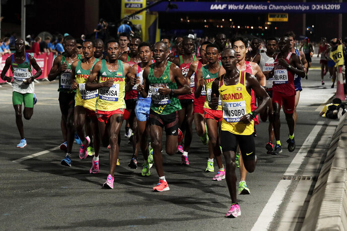 FILE - In this Oct. 6, 2019, file photo, athletes compete during the men's marathon at the World Athletics Championships in Doha, Qatar. Lelisa Desisa, of Ethiopia, won the race. The IOC is seeking to relocate next summer's Olympic marathon from steamy Tokyo to the cooler northern city of Sapporo after seeing competitors collapse in extreme heat at the world championships in Qatar.  (AP Photo/Nariman El-Mofty, File)