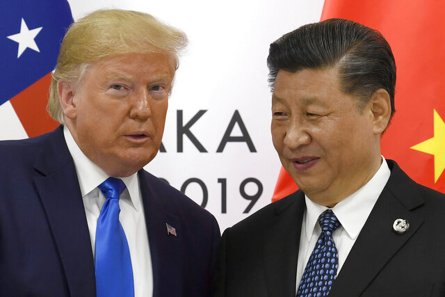 FILE - In this June 29, 2019, file photo, U.S. President Donald Trump poses for a photo with Chinese President Xi Jinping during a meeting on the sidelines of the G-20 summit in Osaka, western Japan. Chinese leaders hope Washington will tone down conflicts over trade, technology and security if Joe Biden wins the Nov. 3 presidential election. But any shift is likely to be in style, not substance, as frustration with Beijing increases across the American political spectrum. (AP Photo/Susan Walsh, File)