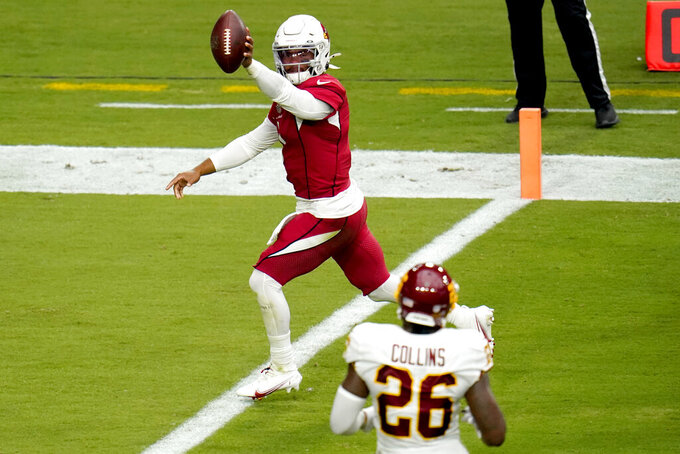 Arizona Cardinals quarterback Kyler Murray (1) scores a touchdown as Washington Football Team strong safety Landon Collins (26) looks on during the first half of an NFL football game, Sunday, Sept. 20, 2020, in Glendale, Ariz. (AP Photo/Ross D. Franklin)