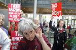 Annette Klapstein listens as Seattle City Council member Kshama Sawant speaks, Tuesday, June 12, 2018, at City Hall in Seattle. Sawant and other members of the Council were expected to vote Tuesday on whether or not to repeal a tax on large companies such as Amazon and Starbucks that was intended to combat a growing homelessness crisis. (AP Photo/Ted S. Warren)
