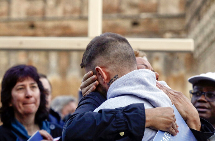 Sex abuse survivor Alessandro Battaglia, right, is hugged by survivor and founding member of the ECA (Ending Clergy Abuse), Denise Buchanan, during a twilight vigil prayer near Castle Sant' Angelo, in Rome, Thursday, Feb. 21, 2019. Pope Francis opened a landmark sex abuse prevention summit Thursday by warning senior Catholic figures that the faithful are demanding concrete action against predator priests and not just words of condemnation. (AP Photo/Gregorio Borgia)