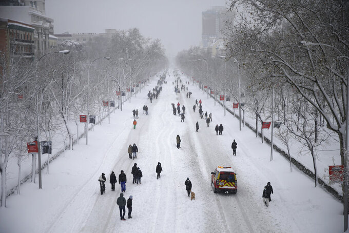 """People walk along """"El Paseo de la Castellana"""" avenue during a heavy snowfall in Madrid, Spain, Saturday, Jan. 9, 2021. A persistent blizzard has blanketed large parts of Spain with 50-year record levels of snow, halting traffic and leaving thousands trapped in cars or in train stations and airports that suspended all services as the snow kept falling on Saturday. (AP Photo/Andrea Comas)"""