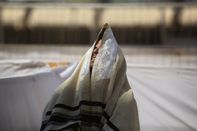 An ultra-Orthodox Jewish man prays ahead of the Jewish new year at the Western Wall, the holiest site where Jews can pray in Jerusalem's old city, Wednesday, Sept. 16, 2020.  A raging coronavirus outbreak is casting a shadow over the normally festive Jewish New Year. With health officials recommending a nationwide lockdown, traditional family gatherings will be muted, synagogue prayers will be limited to small groups and roads will be empty.(AP Photo/Sebastian Scheiner)