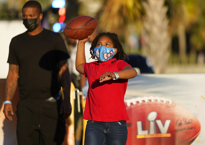 Anaja Brackett throws a football at the NFL Experience for Super Bowl LV Friday, Jan. 29, 2021, in Tampa, Fla. (AP Photo/David J. Phillip)