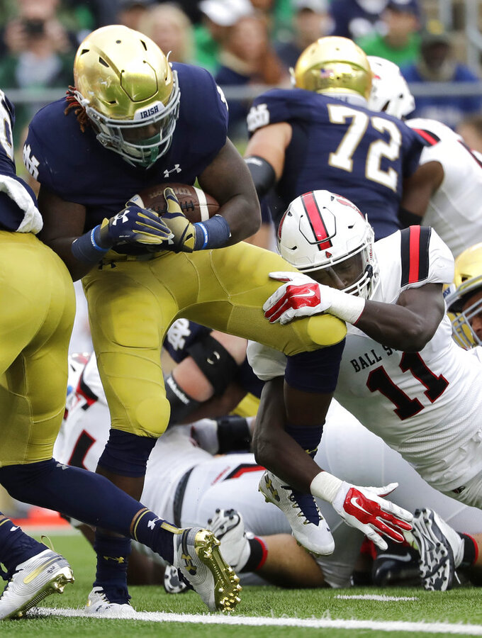 Notre Dame running back Tony Jones Jr., left, scores a touchdown against Ball State linebacker Ray Wilborn during the second half of an NCAA college football game in South Bend, Ind., Saturday, Sept. 8, 2018. Notre Dame won 24-16. (AP Photo/Nam Y. Huh)