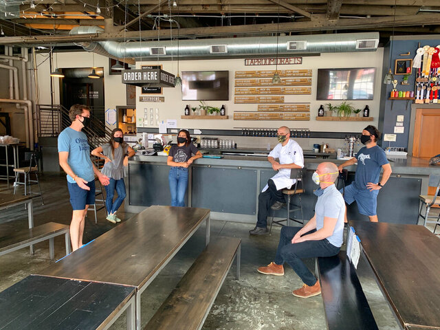 In a July 2020 photo provided by Wolf's Ridge Brewing, owner Bob Szuter, employees Allison Randolph and Alicia Herrmann, sous chef Andy Zamagias, general manager Corey Schlosser and employee Andy Powell, from left, gather inside the restaurant's tap room in Columbus, Ohio. Szuter says he's trying to figure out new ways to bring in revenue, focusing more on the brewery side of the business until it's safe to have a full dining room. (Charlie Wilkerson/Wolf's Ridge Brewing via AP)