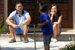 Vicky Li Yip, right, and her husband, Patrick, watch their son Jesse, 5, play outside their home, Friday, July 10, 2020, in Houston. Vicky Li Yip works from home and says online schooling has been exhausting, even with her husband helping out. But with her city becoming a national hot spot, she has been considering what it would mean for her children to face possible exposure every day. (AP Photo/David J. Phillip)