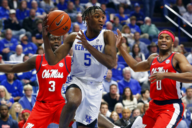 Kentucky's Immanuel Quickley (5) passes near Mississippi's Blake Hinson (0) and Khadim Sy (3) in the first half of an NCAA college basketball game in Lexington, Ky., Saturday, Feb. 15, 2020. (AP Photo/James Crisp)