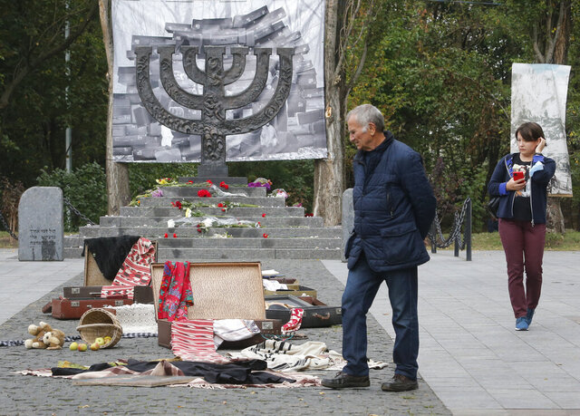 People look an art installation to mark 79th anniversary of the 1941 Babi Yar massacre at a menorah monument close to a Babi Yar ravine where tens of thousands of Jews were killed during WWII, in Kyiv, Ukraine, Tuesday, Sept. 29, 2020. Ukraine marked the 79th anniversary of the 1941 Babi Yar massacre. (AP Photo/Efrem Lukatsky)
