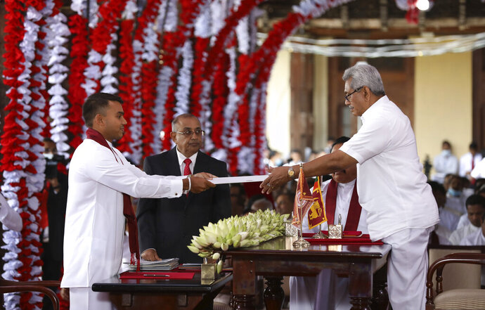 Sri Lankan President Gotabaya Rajapaksa, right, hands over credentials to Namal Rajapaksa, elder son of prime minister Mahinda Rajapaksa after appointing him as the country's sports minister during a ceremony in Kandy, Sri Lanka, Wednesday, Aug. 12, 2020. Sri Lanka's president swore into office a new Cabinet on Wednesday that includes two of his elder brothers and a nephew, after a landslide election victory last week. (AP Photo)