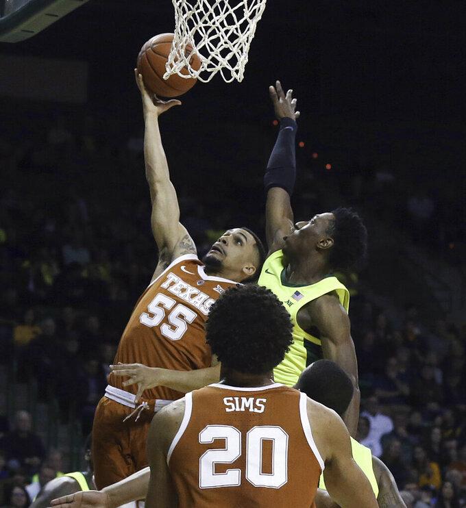 Texas guard Elijah Mitrou-Long (55) scores past Baylor guard Devonte Bandoo during the first half of a NCAA college basketball game Wednesday, Feb. 27, 2019, in Waco, Texas. (Jerry Larson/Waco Tribune Herald via AP)