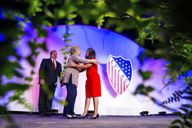 In this July 14, 2016 photo Democratic presidential candidate Hillary Clinton, accompanied by then-LULAC President Roger C. Rocha, Jr., left, hugs University of Texas student Dreamer Lizeth Urdiales, right, as she arrives to speaks at the 87th League of United Latin American Citizens National Convention at the Washington Hilton in Washington. LULAC, the nation's oldest Latino civil rights organization, voted Saturday, Sept. 26, 2020, to postpone its planned national convention in Albuquerque, N.M., in 2021 over uncertainty caused by COVID-19. (AP Photo/Andrew Harnik, File)