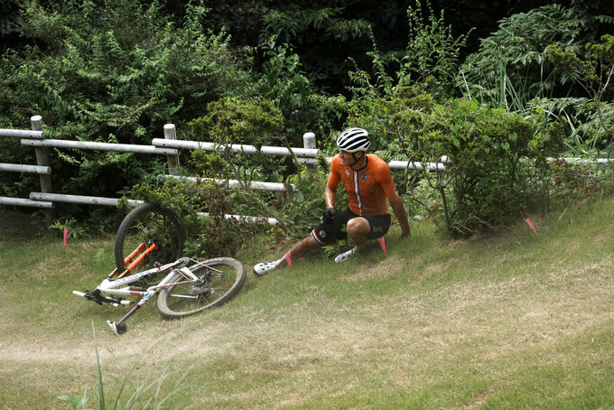 Mathieu van der Poel of the Netherlands gets up after crashing on a downhill during the men's cross country mountain bike competition at the 2020 Summer Olympics, Monday, July 26, 2021, in Izu, Japan. (AP Photo/Thibault Camus)