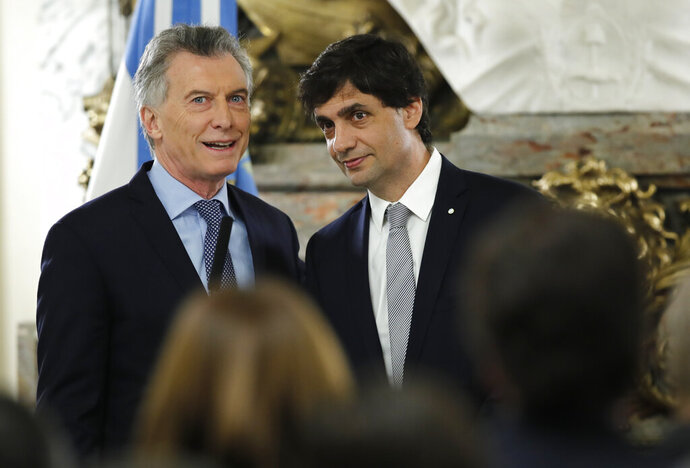 Argentina's President Mauricio Macri, left, talks to new Argentina's Treasury Minister Hernan Lacunza at the government house in Buenos Aires, Argentina, Tuesday, Aug. 20, 2019. Lacunza replaced Nicolas Dujove after the minister resigned. (AP Photo/Natacha Pisarenko)