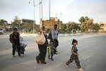 In this photo provided by Rojava Media Center, a pro-Kurdish media group, Syrians carry their belongings, as they flee Ras al Ayn, in northeast Syria, Wednesday, Oct. 9, 2019. (Rojava Media Center via AP)