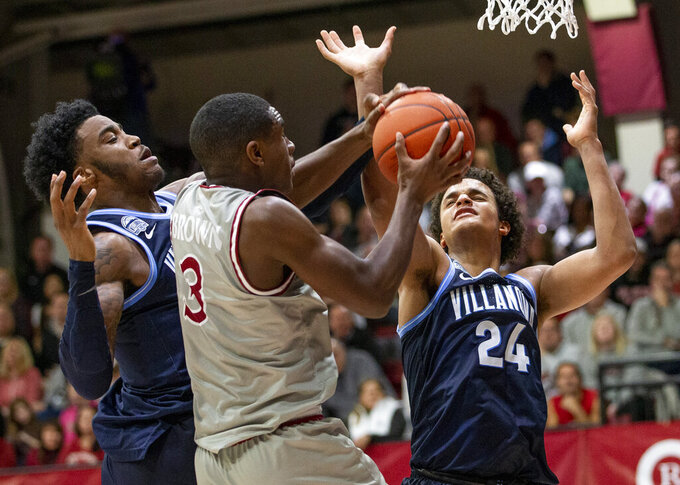 Saint Joseph's guard Cameron Brown (3) grabs a rebound away from Villanova forward Saddiq Bey and forward Jeremiah Robinson-Earl (24) during the second half of an NCAA college basketball game, Saturday, Dec. 7, 2019, in Philadelphia. Villanova won 78-66. (AP Photo/Laurence Kesterson)
