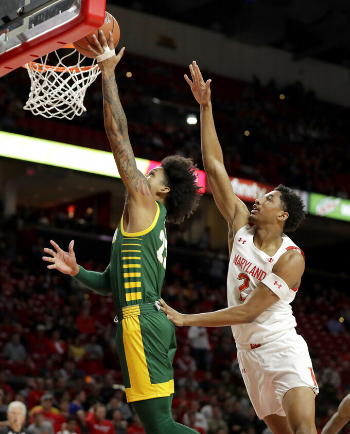 George Mason guard Javon Greene, left, goes up for a shot against Maryland guard Aaron Wiggins during the first half of an NCAA college basketball game Friday, Nov. 22, 2019, in College Park, Md. (AP Photo/Julio Cortez)
